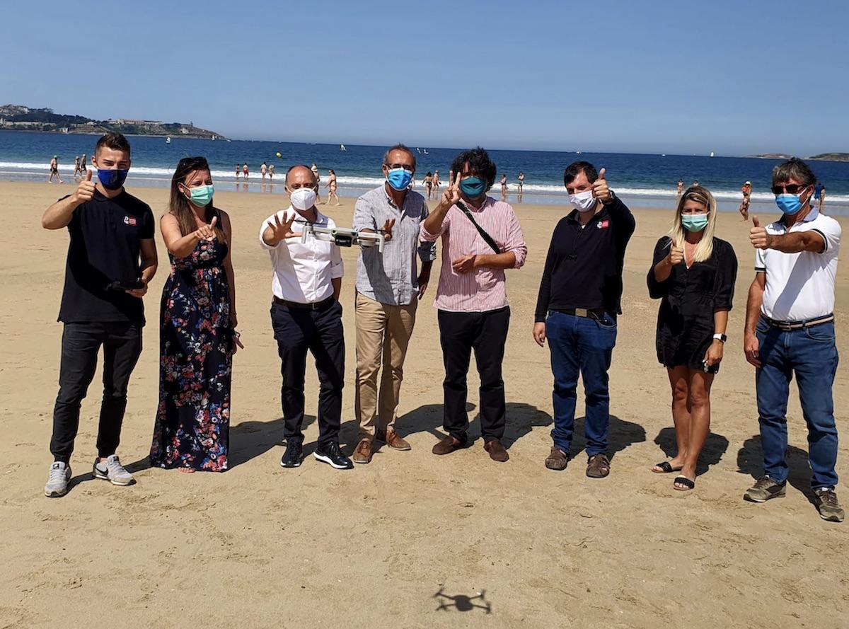 Regades y González probando el dron que controla el aforo de playas, ayer en Praia América. // D.P